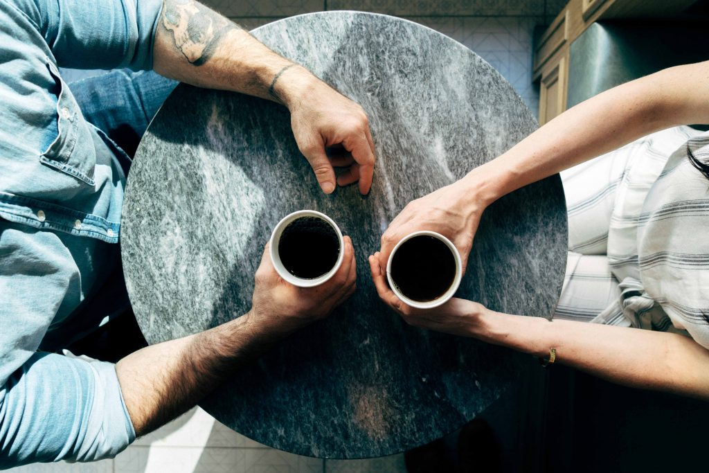 two people having a conversation with coffee