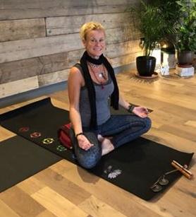 yoga teacher sitting on a mat