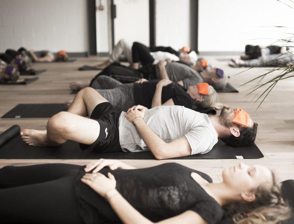 people on yoga mats doing a guided meditation of Yoga Nidra
