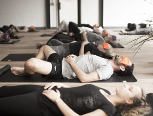 people on yoga mats doing a guided meditation of Yoga Nidra