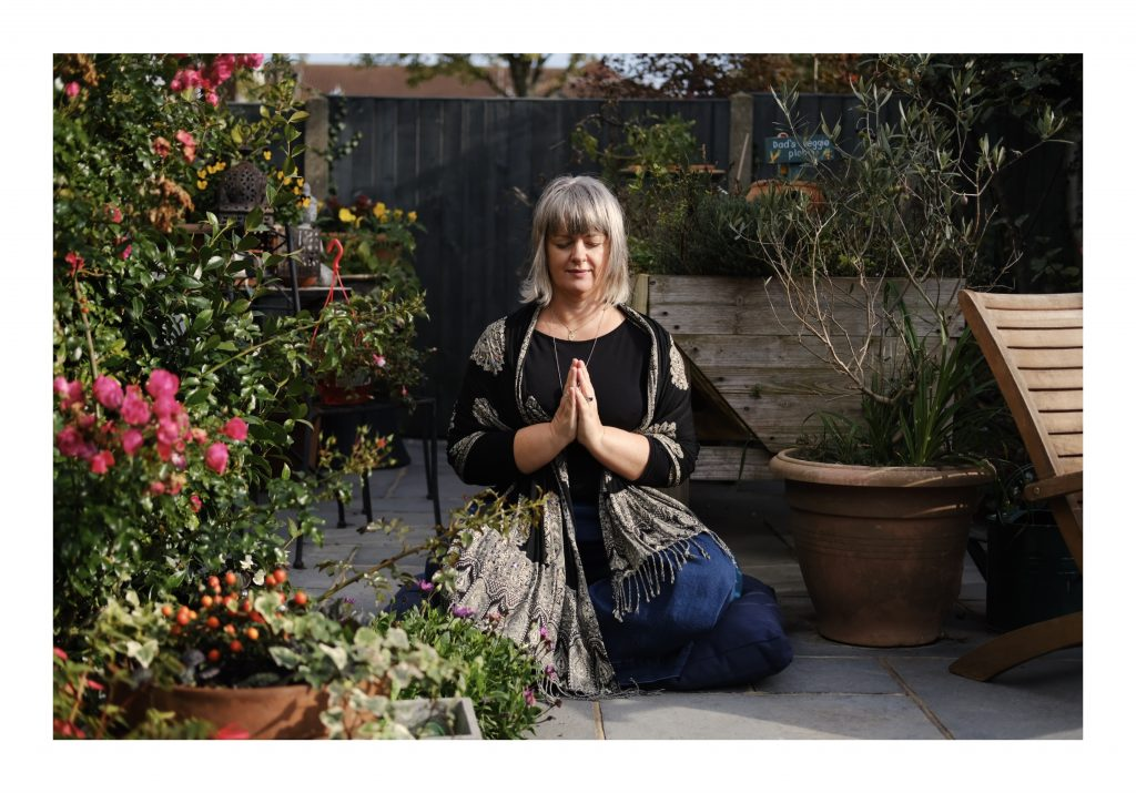 Dawn Lister meditating in a garden