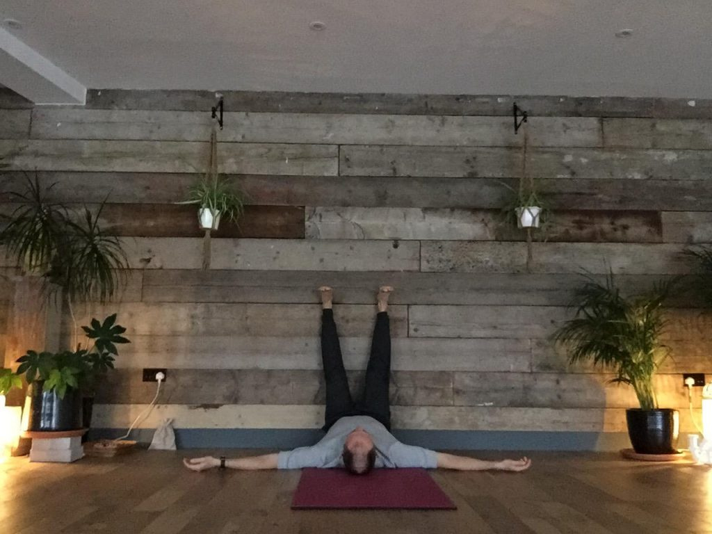 Daniel Groom demonstrating legs up on the wall yin yoga pose