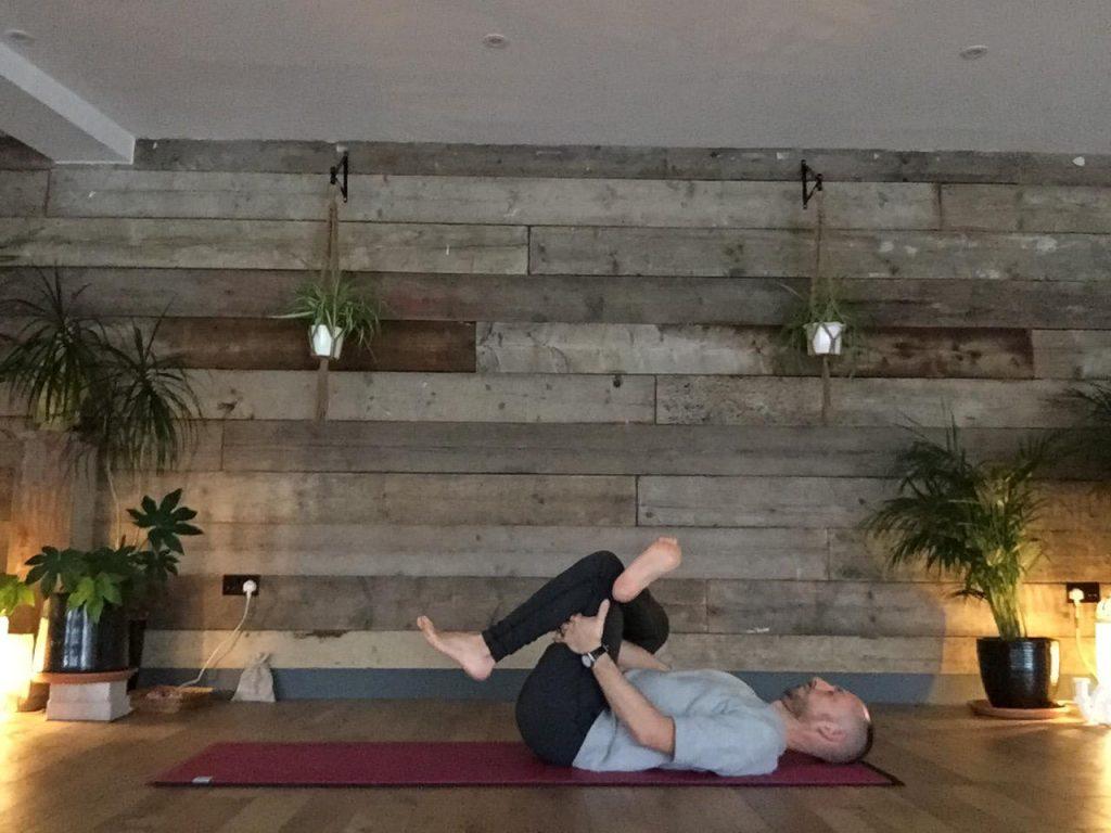 Daniel Groom demonstrating supine pigeon pose from yin yoga