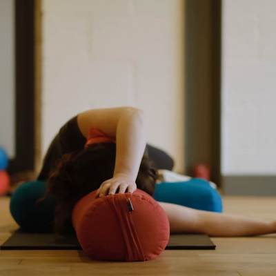 person laying on a cushion doing Rest & Renew yoga
