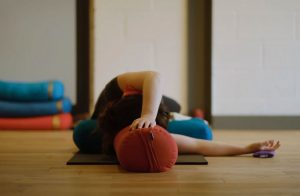 person leaning on cushion during Rest & Renew yoga